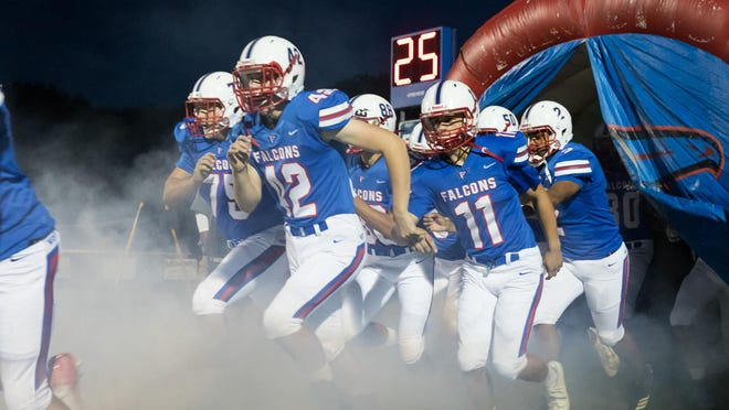 The West Henderson High football players make their way onto the field during last year's home game against Enka.