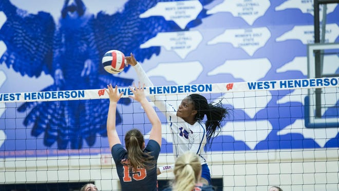 West Henderson's Daija Jackson (15) spikes the ball during the second round of the 3-A state playoffs against Jesse Carson at West.