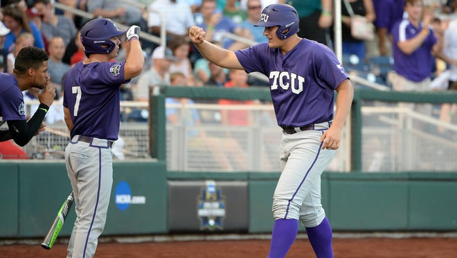 TCU Horned Frogs infielder Luken Baker (19) greets outfielder Josh Watson (7) after scoring in the second inning against the Coastal Carolina Chanticleers in the 2016 College World Series at TD Ameritrade Park.