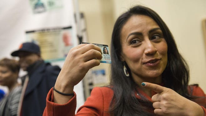 Councilwoman Raquel Castaneda-Lopez, who spearheaded the legislation and was the first recipient of the ID, shows off her card at the Charles H. Wright Museum of African American History on Wednesday.