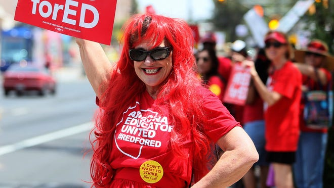 """""""It's our day to be noticed,"""" says Beatrice Goldsmith as she joins approximately a thousand teachers, other staff and supporters on Congress Street at Granada Avenue in Tucson, Ariz., on the first day of the statewide teacher walkout on April Thursday, 26, 2018. (Mamta Popat/Arizona Daily Star via AP)"""