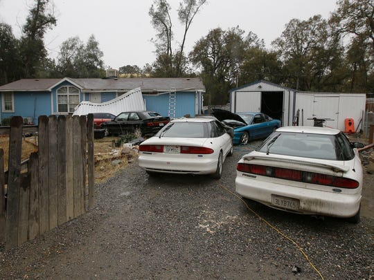 Cars are parked in front of the home of Kevin Janson Neal Wednesday, Nov. 15, 2017, in Rancho Tehama Reserve, Calif. The body of Neal's wife was found at the home, where Neal started his shooting rampage that left four others dead, before he was shot and killed by Tehama County Sheriff's deputies.