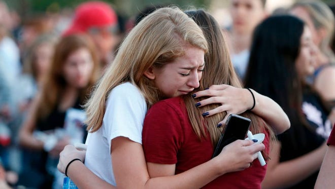 Mourners grieve as they await the start of  a candlelight vigil for victims of the Marjory Stoneman Douglas High School shooting in Parkland, Florida on February 15, 2018.  A former student, Nikolas Cruz, opened fire at the Florida high school leaving 17 people dead and 15 injured. / AFP PHOTO / RHONA WISE        (Photo credit should read RHONA WISE/AFP/Getty Images)