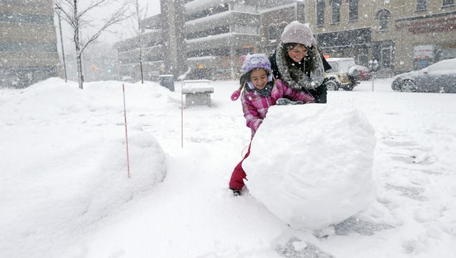 Rachel Wydra and her daughter, Charlize, 5, have fun Tuesday making a snowman at Houdini Plaza in downtown Appleton.