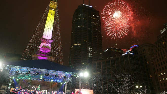 """The """"tree"""" is lit and fireworks begin during Downtown Indy's 54th annual Circle of Lights, presented by Contractors of Quality Connection and Electrical Workers of IBEW #481 on Monument Circle, Indianapolis, Friday, Nov. 25, 2016. Their grandmother Helen Williams watches from behind."""