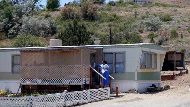 AV Water Co. attorney Germaine Chappelle delivers a notice about a Public Regulation Commission hearing to a residence in the Harvest Gold subdivision near Bloomfield on June 9.