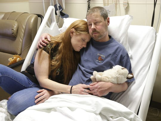 Jason Garcia, 42, holds his stuffed animal named Grumpy Cat as he sits with his wife, Heather, in his hospital bed on Thursday at Milwaukee's Froedtert Hospital.