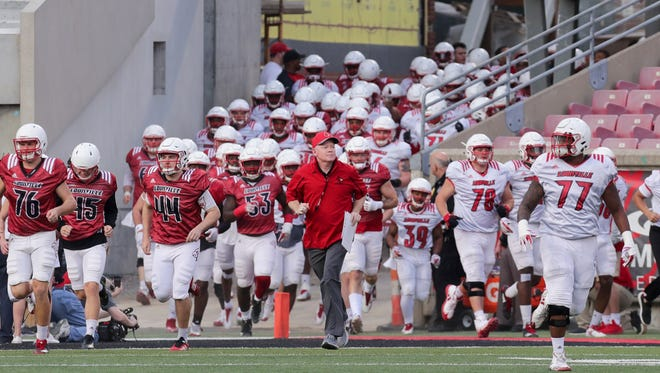 Louisville's Bobby Petrino leads the team on to the field. 