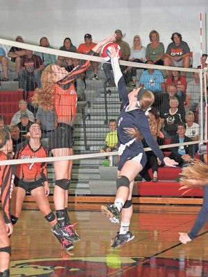 BGM's Bria King, 6, tries to tip the volleyball over the net while Iowa Valley's Ellie Herrmann, 2, blocks the attempt during Iowa Valley's win over the Bears.