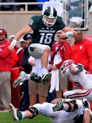 MSU quarterback Connor Cook leaps over lineman Benny McGowan and past Indiana's Chase Dutra for a first down Saturday 10/24/2015.