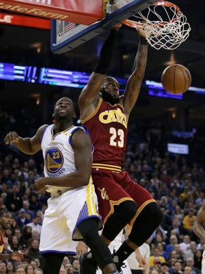 Cleveland's LeBron James, right, scores over former Spartan Draymond Green during the first half on Monday in Oakland.
