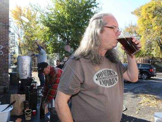 Phil Clarke, the co-owner and manager, samples a beer