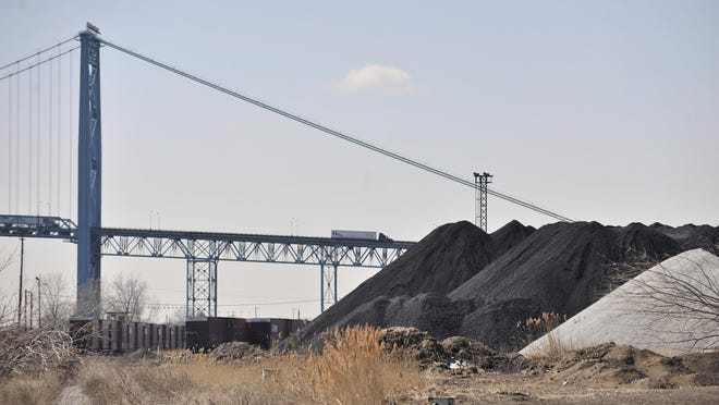 Years after an uproar over 30-foot piles of petroleum coke, above, were stored by a company along the Detroit River, a plan aims to minimize dust exposure.