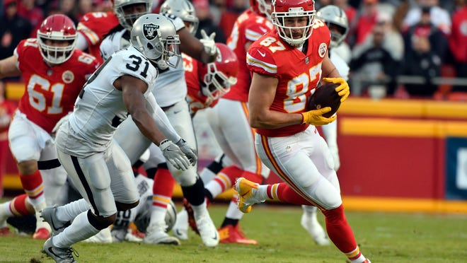 Kansas City Chiefs tight end Travis Kelce (87) makes a catch in front of Oakland Raiders safety Marcus Gilchrist (31) during the first half of an NFL football game in Kansas City, Mo., Sunday, Dec. 30, 2018. (AP Photo/Ed Zurga)