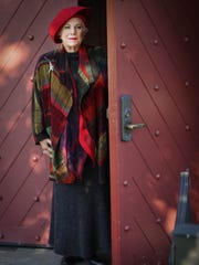 Emily Knox wears a Linea Klub by Kina Fernandez grey outfit; black ankle boots; red wool felt hat; felt and silk scarf by Filz Und Kunzl; amd Marcia Hammond chenille jacket.