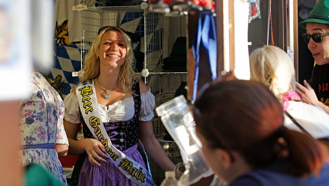 Sigrid Degner laughs inside a booth selling merchandise at Oktoberfest in Glendale in 2014.