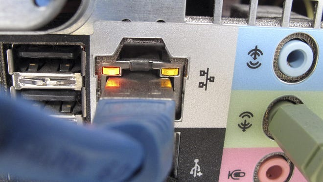 A network cable plugged into the back of a computer is shown.