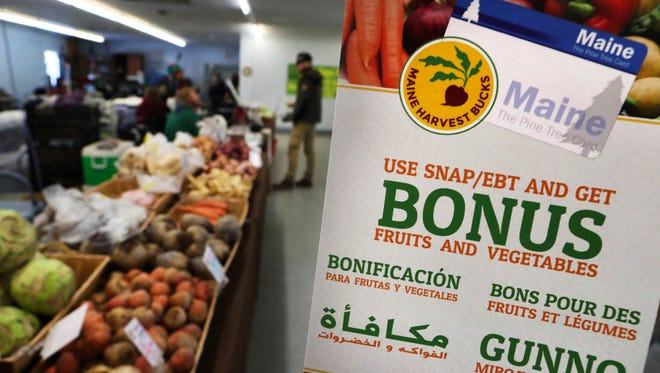 A sign advertises a program that allows food stamp recipients to use their EBT cards to shop at a farmer's market in Topsham, Maine.