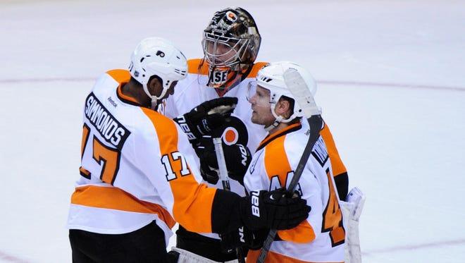 Philadelphia Flyers goalie Steve Mason (35) celebrates with right wing Radim Vrbata (17) and defenseman Kimmo Timonen (44) after beating the Phoenix Coyotes 5-3 at Jobing.com Arena.