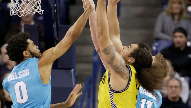 Northern Arizona's Ako Kaluna, right, grabs a rebound against of Gonzaga's Silas Melson (0) and Domantas Sabonis (11) during the second half of an NCAA college basketball game, Wednesday, Nov. 18, 2015, in Spokane, Wash. Gonzaga won 91-52.
