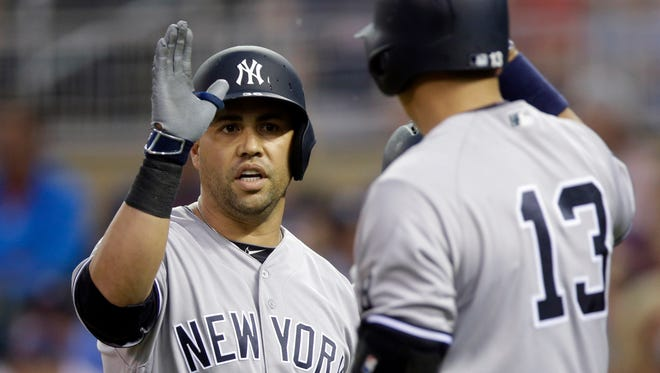 New York Yankees' Carlos Beltran, left, gets a high five from Alex Rodriguez following his two-run home run off Minnesota Twins pitcher Pat Dean in the first inning of a baseball game Friday, June 17, 2016, in Minneapolis.