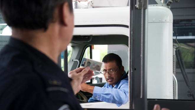 Jesus Cortez, a U.S. Customs and Border Protection officer, checks a driver's paperwork as he brings produce imported from Mexico to the Mariposa Port of Entry in Nogales, Arizona, on Aug. 9, 2017.