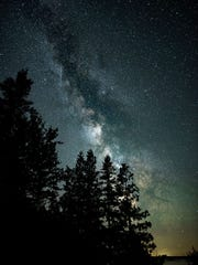The Milky Way is visible above old-growth forest at