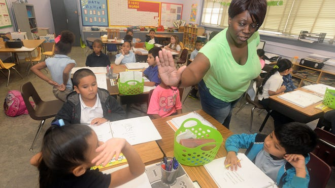 Katrina Bailey gets a high five from a student while teaching a group of first-graders at Creswell Elementary. Creswell is one of the school's that will close if voters approve the school plan and bond issue on May 2.