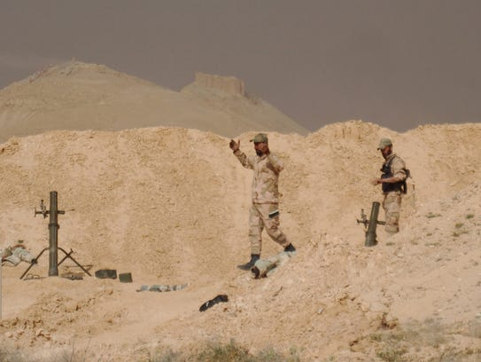 Syrian troops deployed in a field, close to the Palmyra