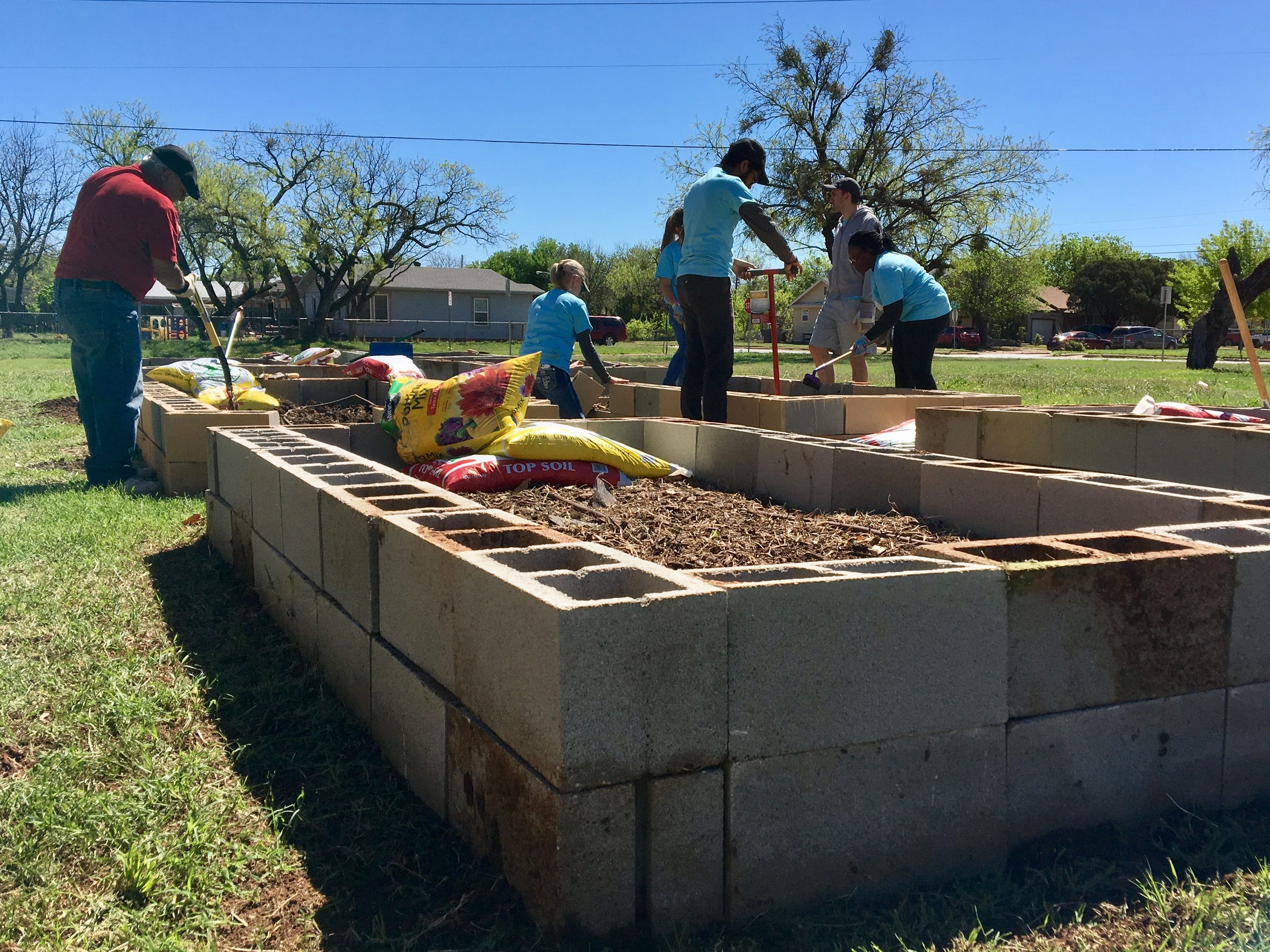 From left: Master Gardener Gilbert  Rodriguez and AmeriCorps VISTA members Terry New, Saul Delgado, I'Esha Baber and Robert McCabe work on garden beds at the Mercy Clinic community garden on March 25, 2017.