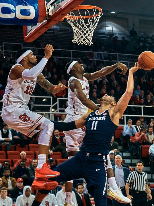Xavier's Kerem Kanter (11) is blocked by St. John's Tariq Owen, center, and Marvin Clark II, left, during the first half of an NCAA college basketball game at Carnesecca Arena in the Queens borough of New York, Tuesday, Jan. 30, 2018. (AP Photo/Andres Kudacki)