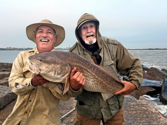 Abel Leal and Glenn Frerich shared in the landing and celebration after catching this big redfish off the San Jose jetty.