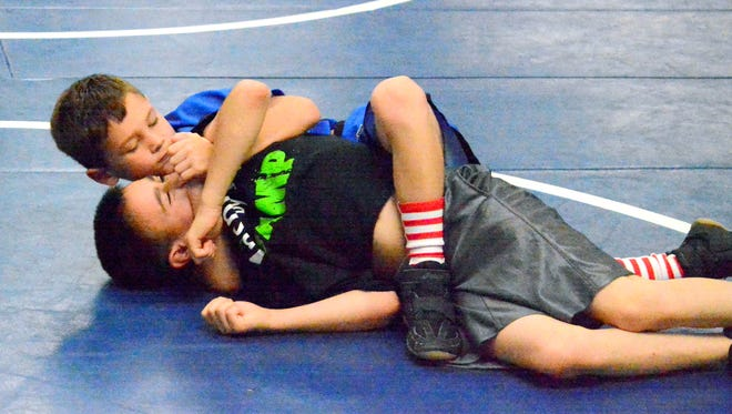 Justin Owens, 8, armlocks Hunter Hartness, 10, during the second annual Team Georgie wrestling camp on Saturday.