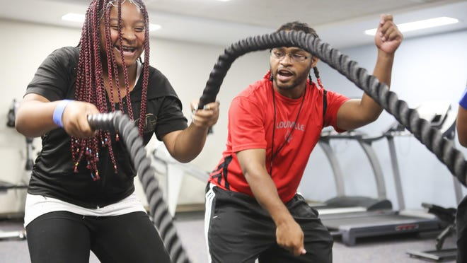 Women's Wellness Camp participant Abriea Jones, left, takes advice from instructor Jamayle West as she swings ropes at the Cabbage Patch Settlement House.