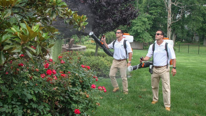Brothers Jeremy Julio (left) and Jason Julio work at a client's house in Little Silver for Last bite Mosquito Control.