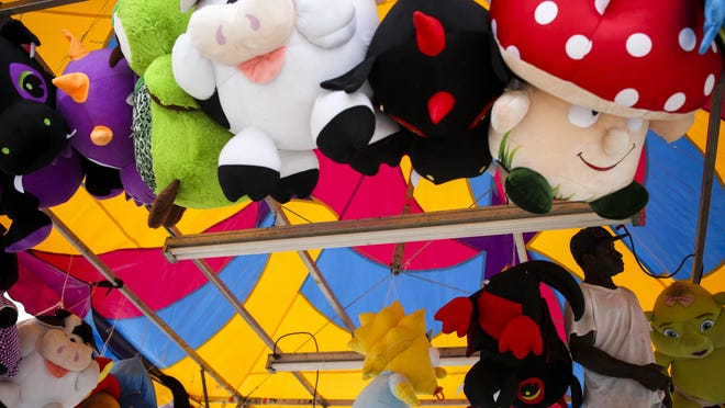 Eddie Wilson hangs stuffed animals in a State Fair tent a the Kentucky Expo Center on Wednesday. Aug. 19, 2015