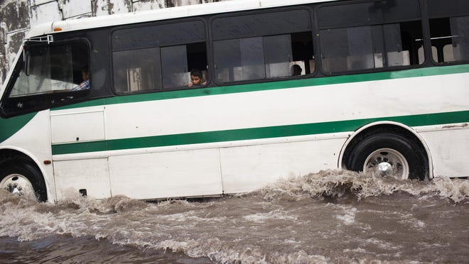 TECOMAN MX - OCTOBER 24: A child looks out a window from a city bus as it drives through a flooded out turn off at the entrance to the city after heavy flooding from Hurriane Patricia October 24, 2015 in Tecoman, Colima, Mexico. Hurricane Patricia struck Mexico's West coast as the most powerful storm ever recorded in the Western Hemisphere but rapidly lost energy as it moved inland. (Photo by Brett Gundlock/Getty Images)