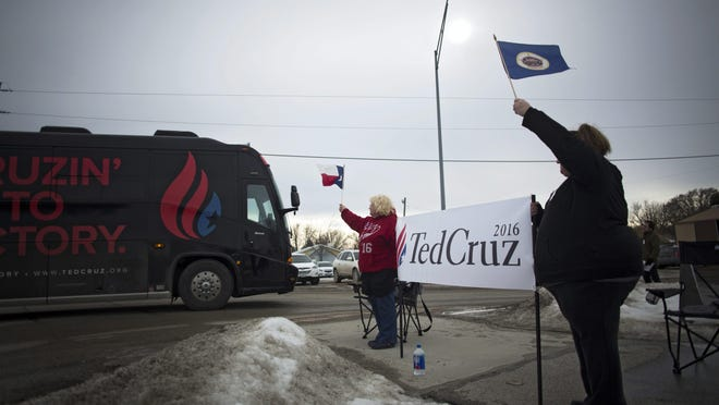 Athena Perez, left, and her daughter Melody Perez wave flags of their home states of Texas and Minnesota as the bus of Republican presidential hopeful Ted Cruz passes them as he arrives at Darrell's Place for a campaign event in Hamlin, Iowa on Jan. 30.