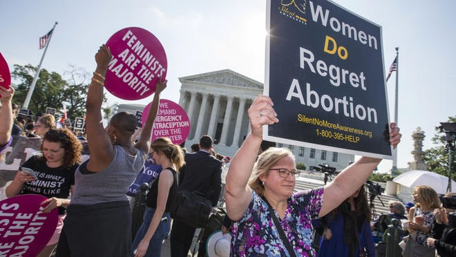 Activists demonstrate in front of the Supreme Court in Washington, D.C., on June 27, 2016, as the justices close out the term.  Dcisions on abortion, guns and public corruption are expected. (AP Photo/J. Scott Applewhite)
