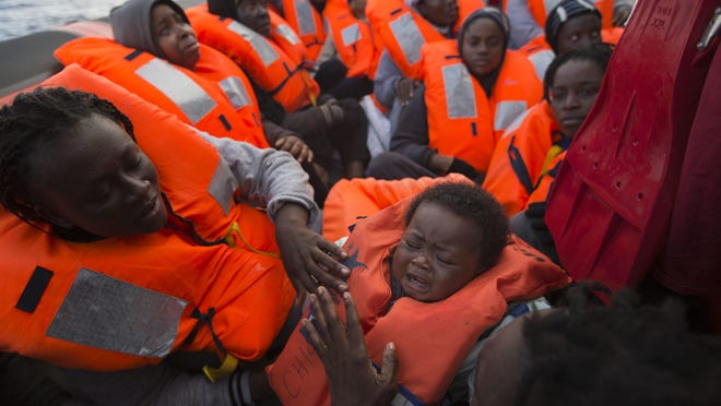 Migrants and refugees are assisted by members of the Spanish NGO Proactiva Open Arms, as they crowd aboard a wooden boat sailing out of control in the Mediterranean Sea about 21 miles north of Sabratha, Libya, on Friday.