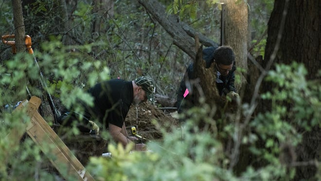 In this Monday, Oct. 22, 2018 photo, detectives investigate the scene where remains believed to be those of a southwestern Michigan woman who disappeared in 2010 were found, in Fulton, Mich. Doug Stewart, who was convicted of killing his estranged wife in 2011, took police to the burial site Monday.