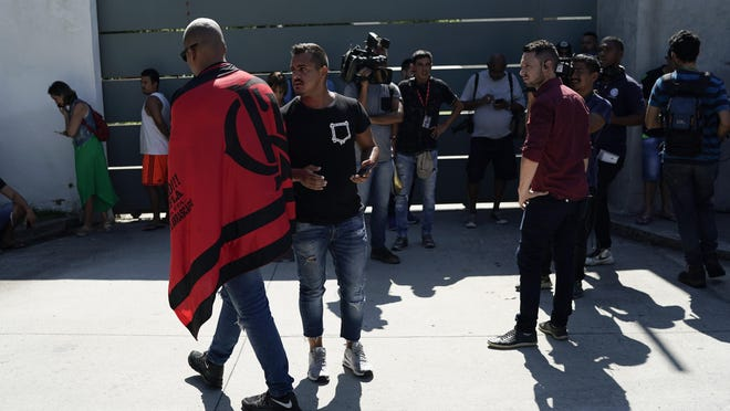 Friends, fans and journalists stand at the entrance of the Flamengo soccer training center as they wait for information after a fire in the facilities of the soccer club in Rio de Janeiro, Brazil, Feb. 8, 2019. Firefighters say a number of people have died in an early morning fire at a training facility of one Brazil's largest soccer clubs.