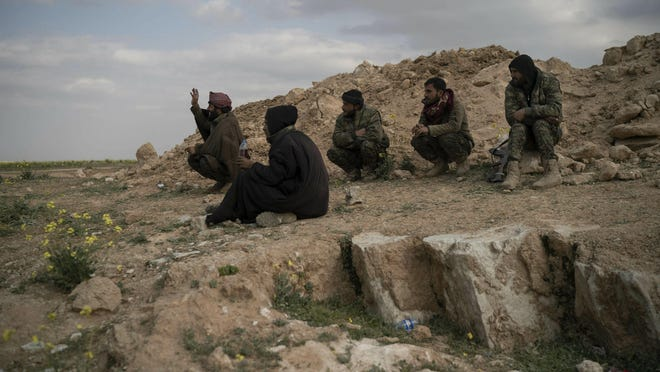 U.S.-backed Syrian Democratic Forces (SDF) fighters sit atop a hill in the desert outside the village of Baghouz, Syria, Feb. 14, 2019. U.S.-backed Syrian forces are clearing two villages in eastern Syria of remaining Islamic State militants who are hiding among the local population, and detaining others attempting to flee with the civilians, the U.S.-led coalition said Thursday.