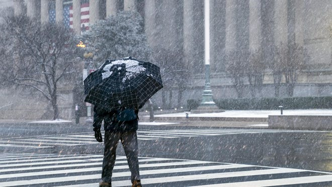 A man crosses Constitution Avenue near the National Archives as a winter snow storm hits the nation's capital closing Federal offices and all major public school districts around Washington, Feb. 20, 2019.