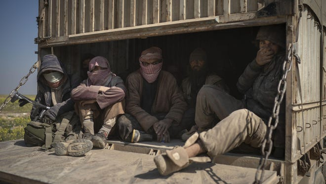 Men ride in the back of a truck that is part of a convoy evacuating hundreds out of the last territory held by Islamic State militants in Baghouz, eastern Syria, Feb. 20, 2019. The evacuation signals the end of a week long standoff and opens the way to U.S.-backed Syrian Democratic Forces (SDF) recapture the territory.