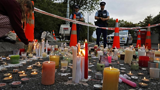 In this March 18, 2019, file photo, a student lights candle during a vigil to commemorate victims of March 15 shooting, outside the Al Noor mosque in Christchurch, New Zealand.