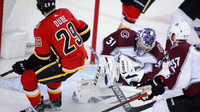 Colorado Avalanche goalie Philipp Grubauer, right, stops a shot from Calgary Flames' Dillon Dube during third period NHL hockey action in Calgary, Tuesday, Nov. 19, 2019. (Jeff McIntosh/The Canadian Press via AP)