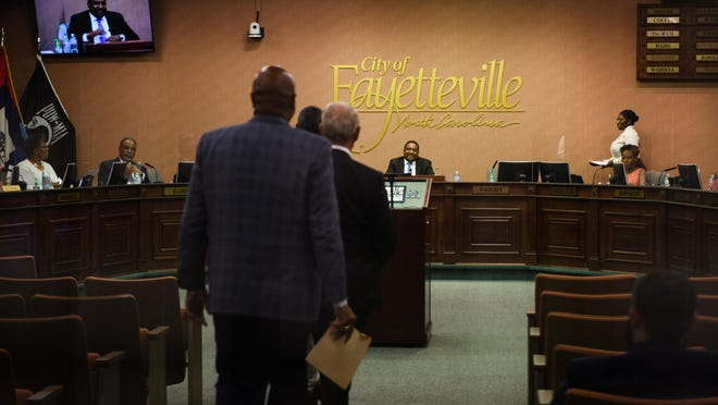 Mayor Mitch Colvin smiles as the Rev. Chris Stackhouse of Lewis Chapel Baptist Church, the Rev. Brian Thompson of Simon Temple AME Zion Church and Pastor Al Brice of Covenant Love Church approach the podium to address the City Council about tearing down the Market House on Monday.