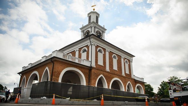 The city places fencing around the Market House on Friday. The building was damaged last month when people set it on fire.
