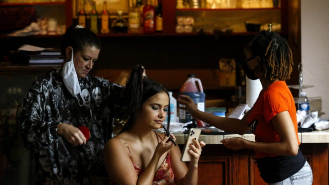 "Melanie Harrah, left, and Latonia Brown, right, do hair and makeup Saturday for Mercedes Gutierrez, the actress playing the character Lia Lopez, behind the scenes of the horror-thriller movie ""Call Time."" The film is being shot in Alachua."